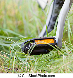 Closeup of a pedal of a bicycle outdoors.