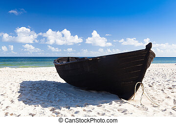 Black fishing boat on the beach on Ruegen Island, Germany
