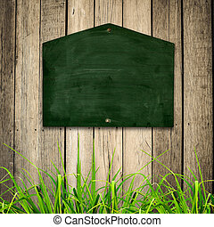 Blackboard with green grass on wooden background.