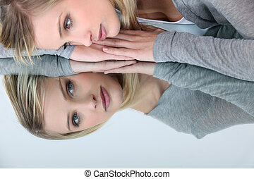 blonde woman looking her reflection in a mirror