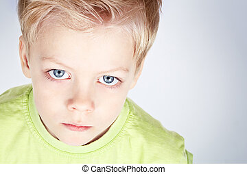Close-up portrait of a charming blue-eyed boy gazing at camera