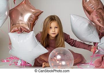 blue-eyed cute girl in dress sitting on floor with balloons on a white background