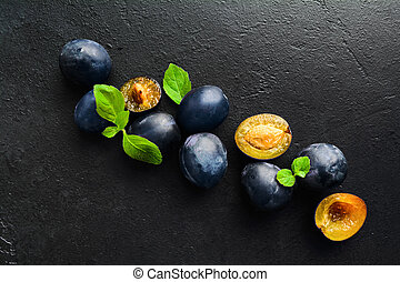 Blue fresh natural organic healthy plums with green mint leaves with copy space