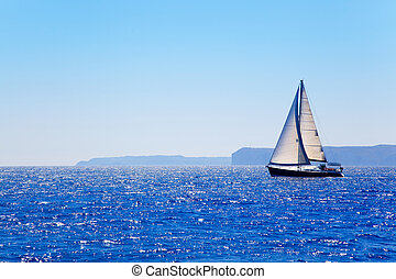 Blue Mediterranean sailboat sailing in perfect ocean at San Antonio cape