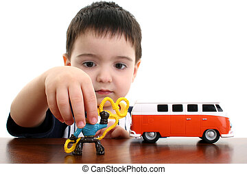 Toddler boy playing with toy car and cowboy. Shot in studio over white.