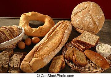 Bread still live over dark wood background, varied shapes