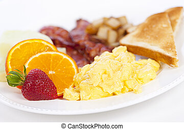 Delicious breakfast of scrambled eggs toast and bacon