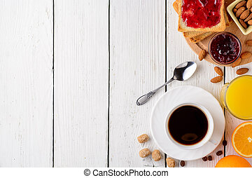 Breakfast table with healthy tasty ingredients. Coffee, toast, jam, almonds, orange juice and fruit on white wooden background.
