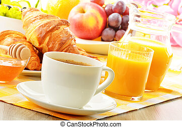 Breakfast with coffee, orange juice, croissant, egg, vegetables and fruits