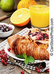 Breakfast with orange juice, fresh croissant and cake