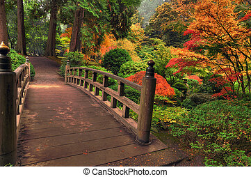 Historic wooden bridge in a park surrounded by autumn colors in a foggy morning