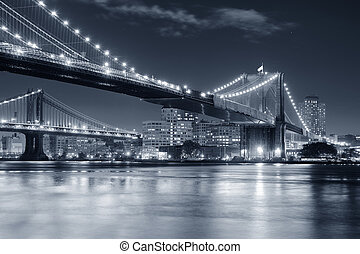 Brooklyn Bridge over East River at night in black and white in New York City Manhattan with lights and reflections.