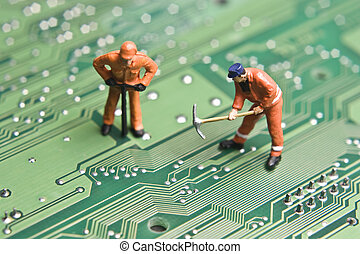 Worker figurines posed to look as though they are working on a computer circuit board.