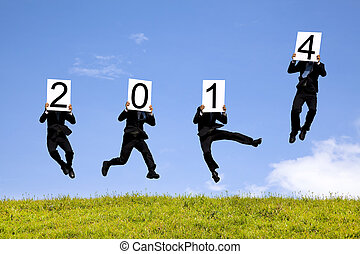 business man jumping with 2014 year text on the grass