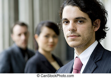 A young businessman standing in front of two colleagues (shallow depth of field used)