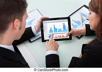 Business People Discussing Over Graphs On Digital Tablet