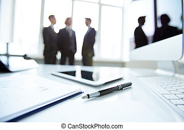 Business devices and document at workplace, unrecognized businesspeople sharing ideas on background