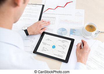 Businessman at the workplace working with documents and using modern digital tablet.