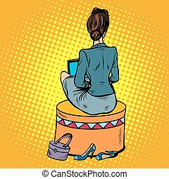 businesswoman sits back on the couch pop art retro style. The girl with the laptop. New technologies. Comfortable furniture