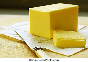 Block of butter, cut, on old chopping board, with bone-handled knife.