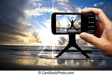 Camera mobile phone and happy jumping man on the beach at beautiful sunrise