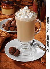 A cup of cappuccino with whipped cream and truffles