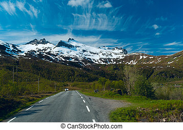 Car on the asphalt road to Norvegian mountains in sunny clear day