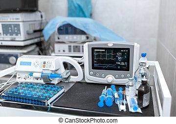 Cardiac monitor and syringe at operating table. Pet surgery