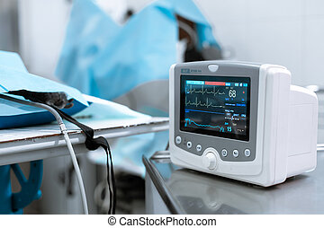 Cardiac monitor at operating table with dog on background. Pet surgery