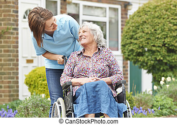 Carer With Senior Woman In Wheelchair