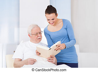 Young female caretaker and senior man reading book together in nursing home