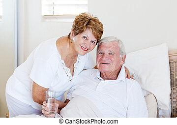caring senior wife taking care of ill husband