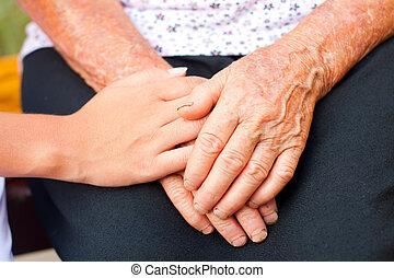 Young hands between elderly ones.