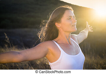 Beautiful young woman stretching her arms joyfully praising the beauty of Life.