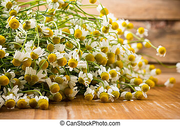 Chamomile flowers on a wooden surface.