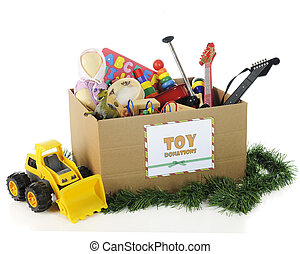 """A large corrugated box with a """"Toy Donations"""" sign. Its filled with assorted toys and surrounded by Christmas garland and a toy bulldozer. On a white background."""