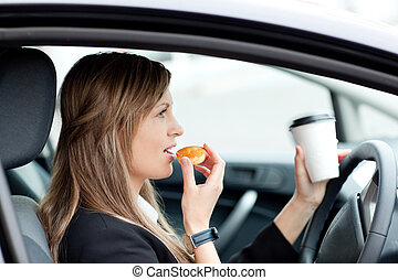 Charming businesswoman eating and holding a drinking cup while driving to work