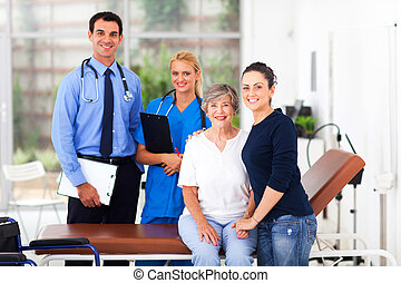 cheerful elderly patient and her daughter in hospital with doctor and nurse