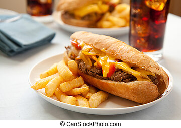 cheesesteak sandwich accompanied by fries and an ice cold cola