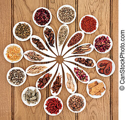 Large chinese herbal medicine selection in white porcelain dishes over oak background.