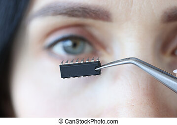 Chip is inserted into womans eye with tweezers closeup