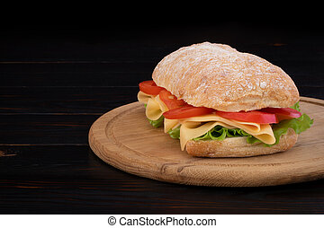 Ciabatta sandwich with lettuce , prosciutto and cheese on wooden board with copy space