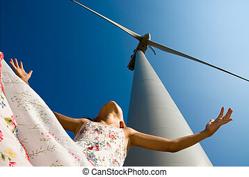 girl playing in the wind under a turbine