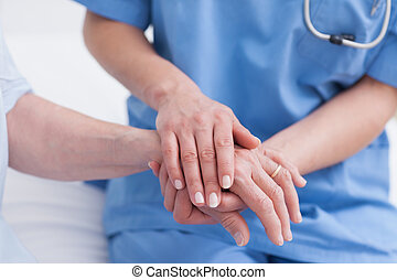 Close up of a nurse touching hand of a patient in hospital ward