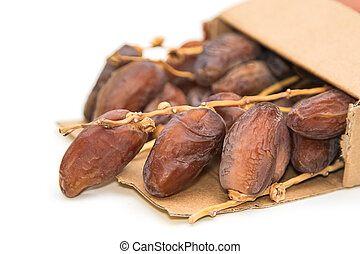 close up of dried dates in paper box on white background