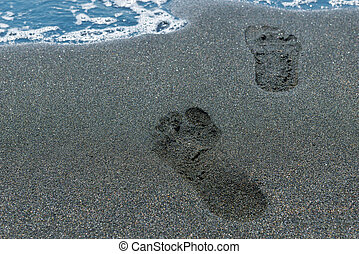 close-up of footprints in the sand on the beach