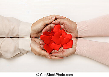 Close-up of the hand of an adult daughter and an older mother, holding together many hearts in their palms. Top view. Family and care concept