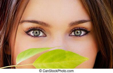 closeup of beautiful eyes and green leave below
