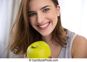 Closeup portrait of a smiling young woman with green apple