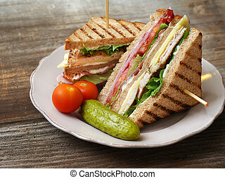 Photo of a club sandwich made with turkey, bacon, ham, tomato, cheese, lettuce, and garnished with a pickle and two cherry tomatoes.